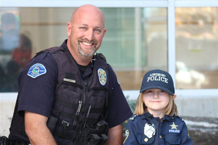 Sidney Fahrenbruch, 4, posed alongside Longmont Police Officer David Bonday, who helped the little girl by checking for monsters on an earlier visit.