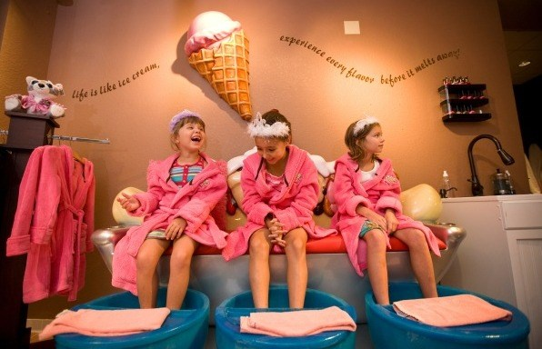 Děti don pink robes and tiaras at the ice cream-themed Scooops Spa at Great Wolf Lodge.