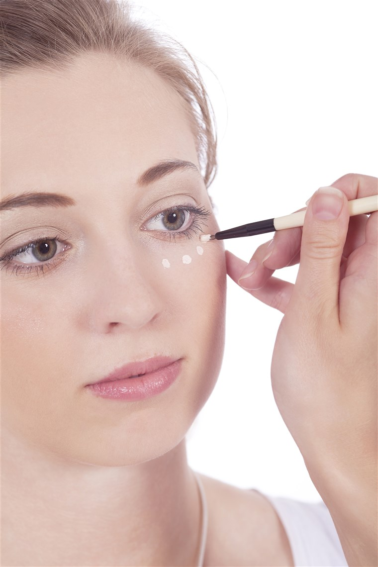 жена applying concealer