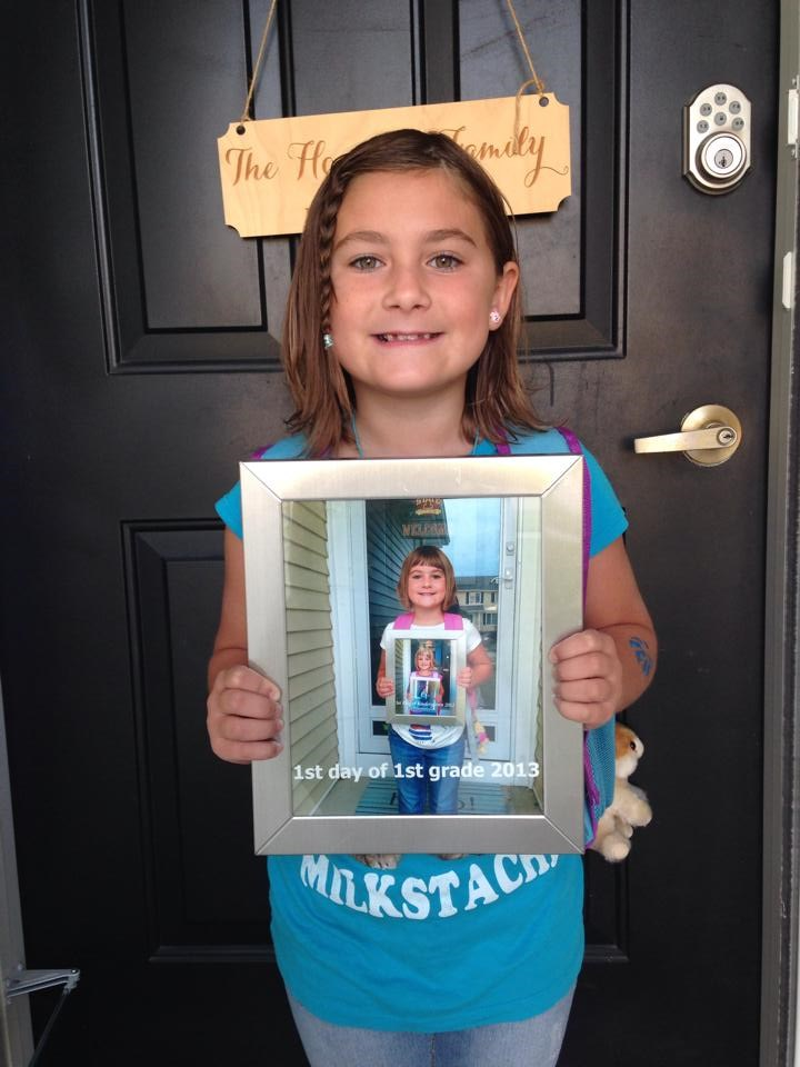 Začíná 2nd grade by holding a pic of what she looked like starting 1st grade.
