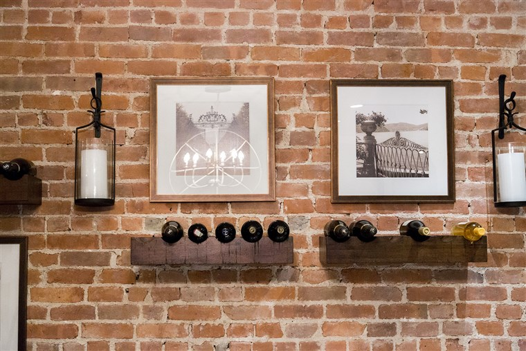 Дилън and her husband decided to store their wine bottles by creating a wine display on an exposed brick wall near the kitchen.