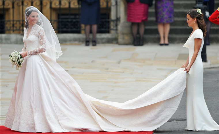 Kate Middleton is helped at her wedding by sister Pippa.