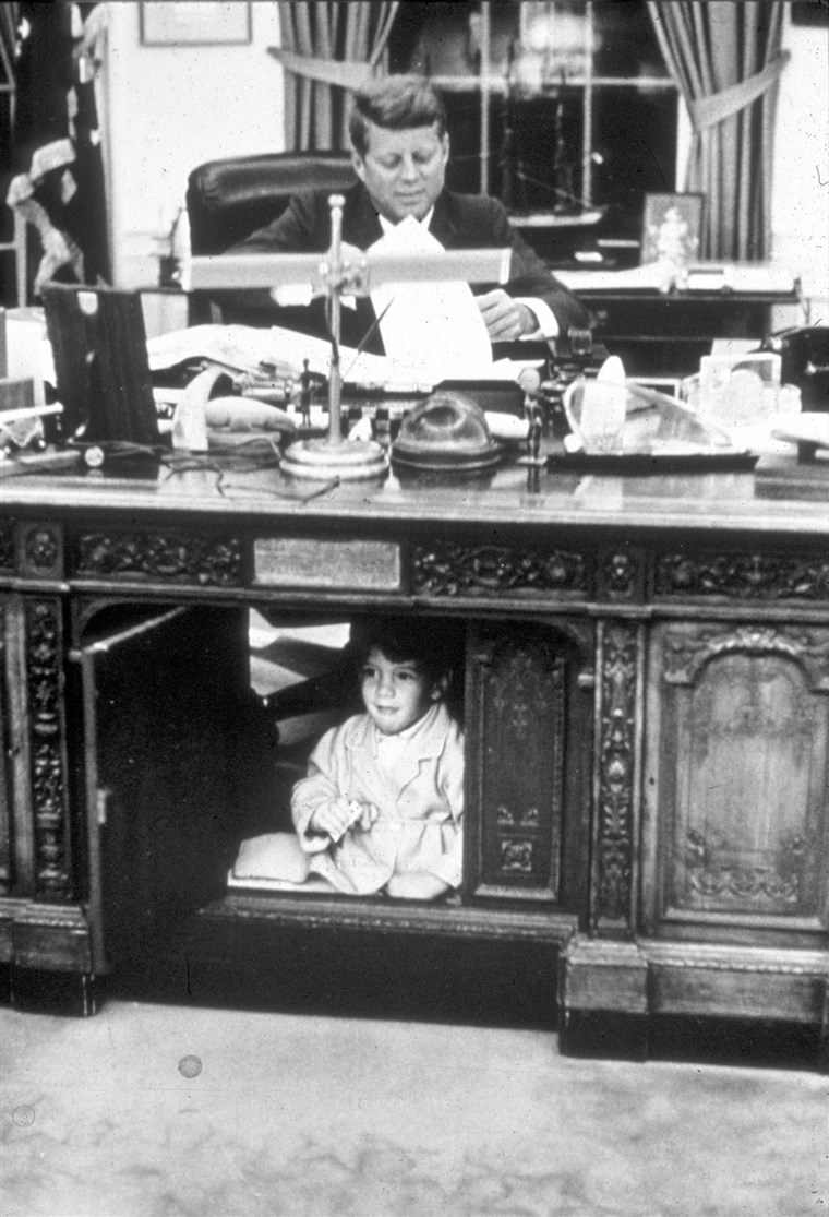 John F. Kennedy Jr. hides in his father's Oval Office desk in October 1963.