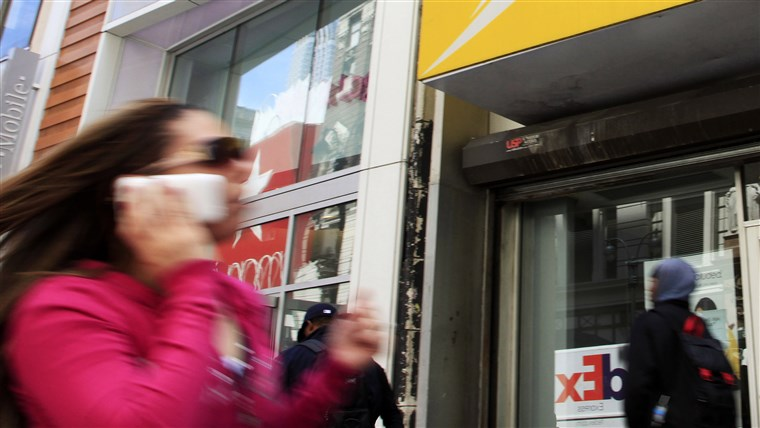 А woman using a cell phone walks past T-Mobile and Sprint stores, Tuesday, April 27, 2010, in New York. Sprint Nextel Corp. on Wednesday, April 28, sa...