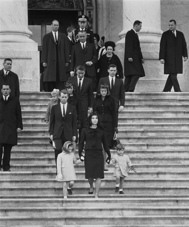 Кенеди family members descend steps in Washington, Nov. 25, 1963, at the funeral for President John F. Kennedy. From front to back at left are: Caroline Kennedy, Jacqueline Kennedy and John Kennedy Jr.; behind them, Robert F. Kennedy, Patricia Kennedy Lawford and her husband, Peter Lawford; Little Sydney Lawford is at left of her mother. Behind Mrs. Kennedy are Jean Kennedy Smith and her husband Stephen E. Smith. Near top are President Lyndon B. Johnson and his wife Lady Bird Johnson. Behind the vice president is the chairman of the Joint Chiefs of Staff, Maxwell D. Taylor.