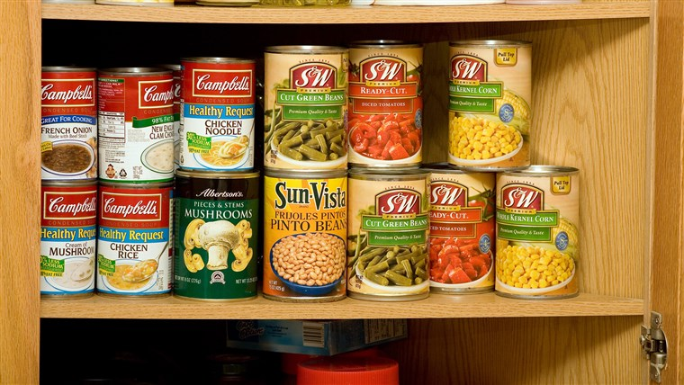 дървен kitchen cupboard with shelves full of canned soup and vegetables