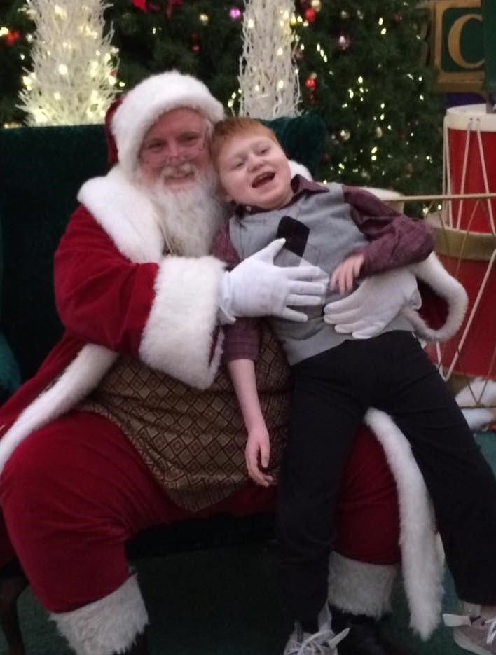 Maggie Dunham says her son, Will, takes longer than most to get set up for his photo due to his use of a wheelchair, but never feels rushed by Santa Scott and his team.