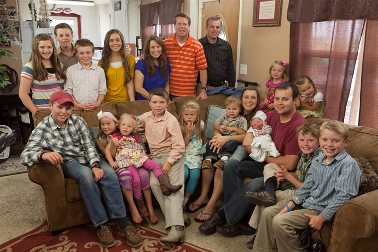 Най- whole Duggar family meets baby Marcus, who is in his father's arms.