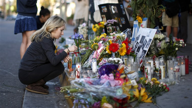EIN woman lights a candle at a makeshift shrine for 20-year-old UCSB student Christopher Michael-Martinez outside a deli that was one of nine crime scen...